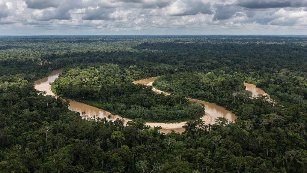 Photo of the Amazon rainforest in Peru, with a river winding through it