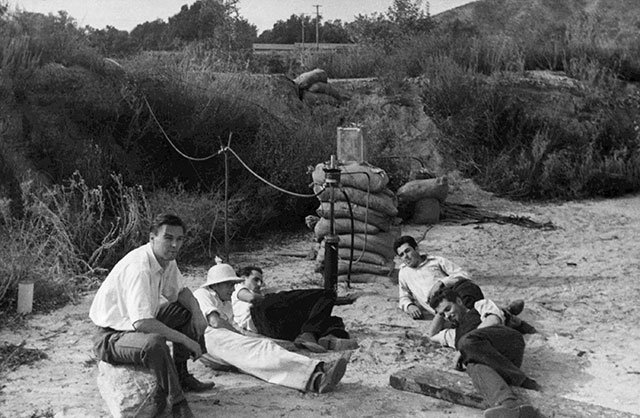 A black and white photo shows a desert scrub area. Five men lay on the ground and behind them is a rudimentary rocket motor with hoses leading to a device proped up on a stack of sandbags.