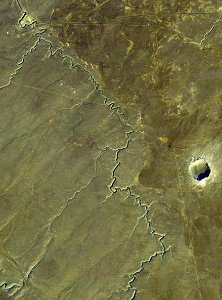 This view acquired by NASA's Landsat 4 satellite on December 14, 1982, shows Barringer Crater, also known as 'Meteor Crater,' a deep hole in the flat-lying desert sandstones west of Winslow, Arizona.