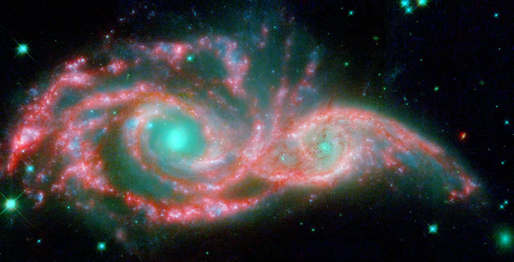 NASA's Hubble and Spitzer telescopes combined to make these shape-shifting galaxies taking on the form of a giant mask. The icy blue eyes are actually the cores of two merging galaxies, called NGC 2207 and IC 2163, and the mask is their spiral arms.
