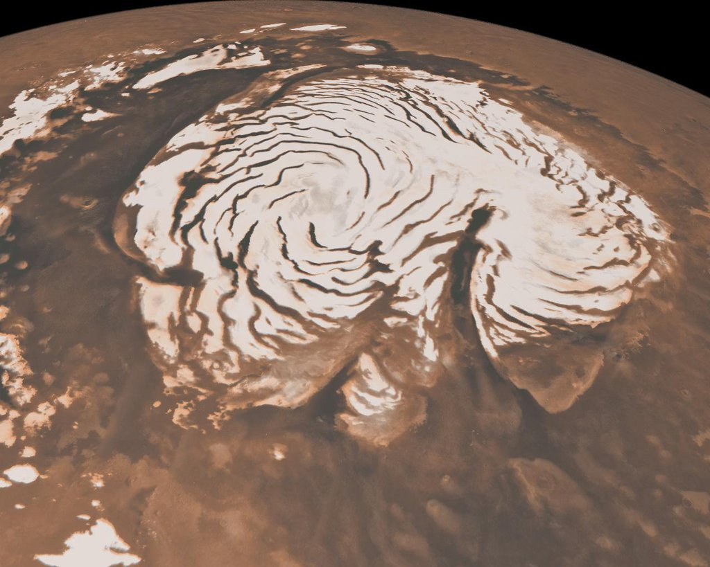 This image, combining data from two instruments aboard NASA's Mars Global Surveyor, depicts an orbital view of the north polar region of Mars. To the right of center, a large canyon, Chasma Boreale, almost bisects the white ice cap.