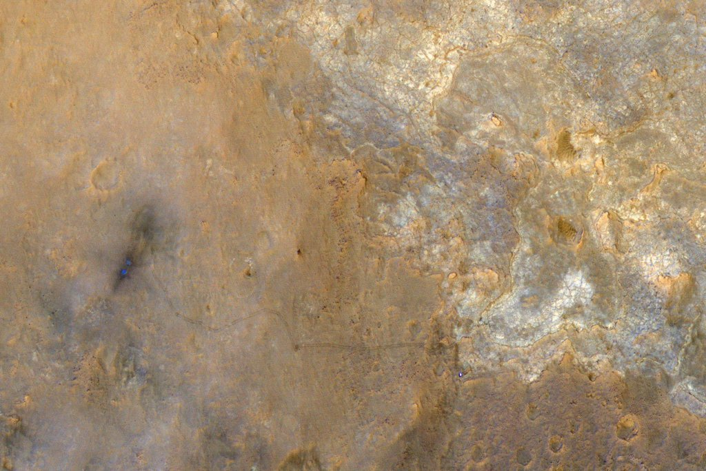 NASA's rover Curiosity appears as a bluish dot near the lower right corner of this enhanced-color view from the HiRISE camera on NASA's Mars Reconnaissance Orbiter.