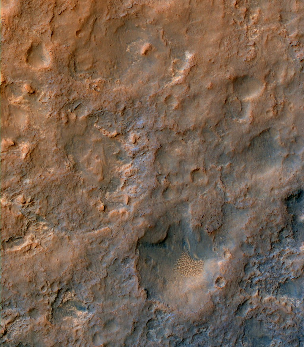 Two parallel tracks left by the wheels of NASA's Curiosity Mars rover cross rugged ground in this portion of an observation by the HiRISE camera on NASA's Mars Reconnaissance Orbiter on Dec. 11, 2013. The rover itself does not appear in this image.