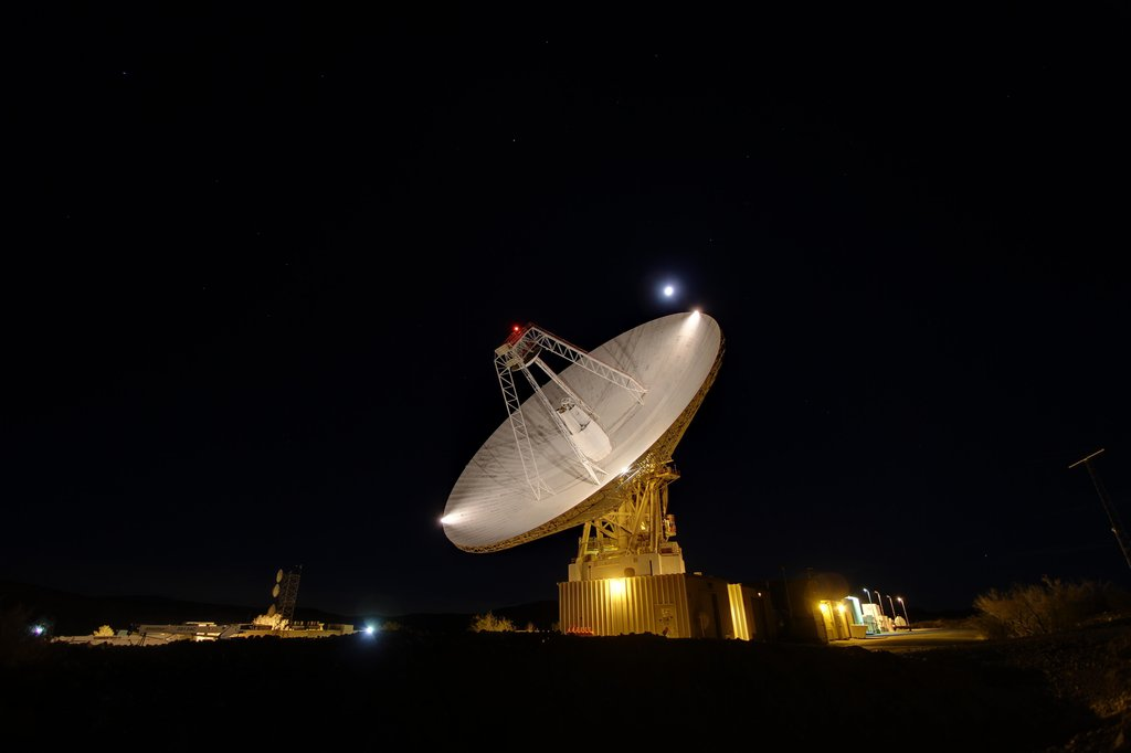 Goldstone's 230-foot (70-m) antenna tracks under a full moon. The Goldstone Deep Space Communications Complex is located in the Mojave Desert in California, USA.