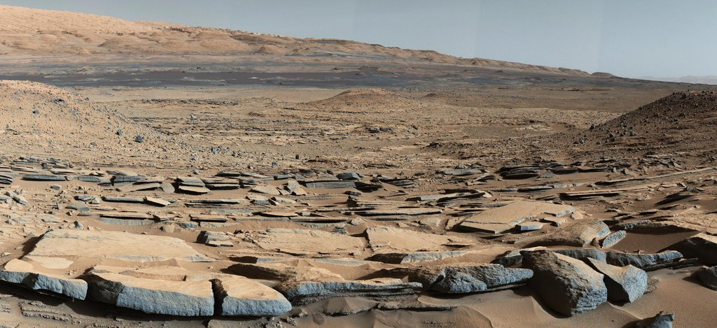 A view from the 'Kimberly' formation on Mars taken by NASA's Curiosity rover. The strata in the foreground dip towards the base of Mount Sharp, indicating the ancient depression that existed before the larger bulk of the mountain formed.