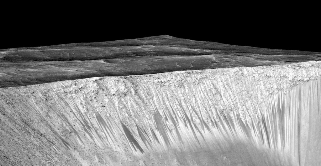 Dark narrow streaks, called 'recurring slope lineae,' emanate from the walls of Garni Crater on Mars, in this view constructed from observations by the HiRISE camera on NASA's Mars Reconnaissance Orbiter.
