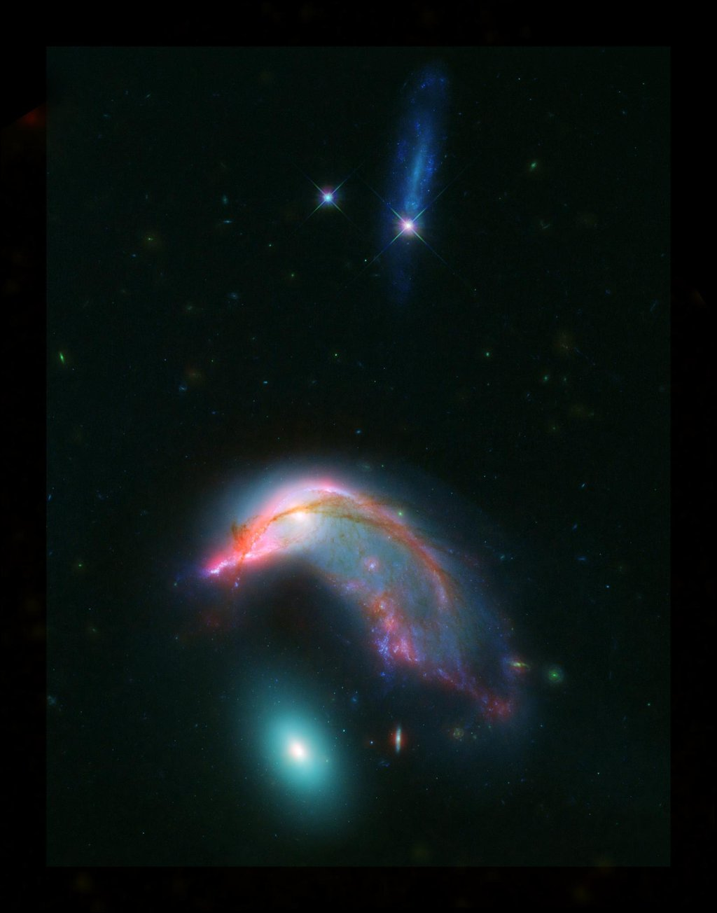 This image of distant interacting galaxies, known collectively as Arp 142, bears an uncanny resemblance to a penguin guarding an egg. Data from NASA's Spitzer and Hubble space telescopes have been combined to show these dramatic galaxies.