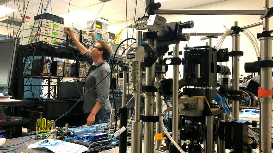 This image shows NASA Cold Atom Laboratory's physicist David Aveline working in the CAL test bed, which is a replica of the CAL facility that stays on Earth.