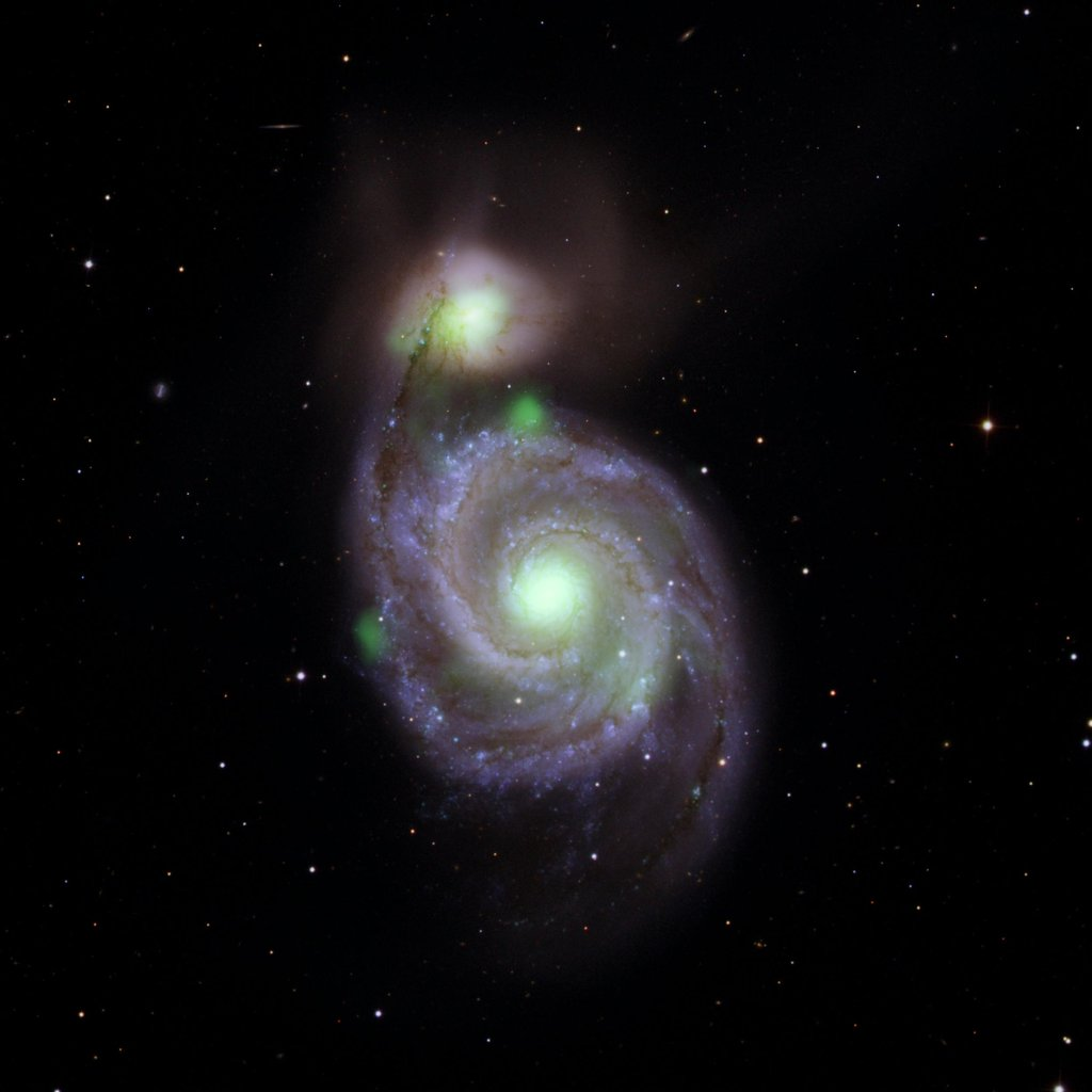Sources of high-energy X-ray light captured by NASA's NuSTAR mission are overlaid on an image of the Whirlpool galaxy and its companion galaxy, M51b, taken by the Sloan Digital Sky Survey.