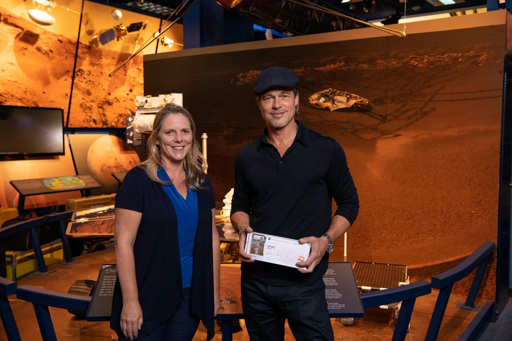 The actor Brad Pitt (right) shows off his 'boarding pass' for Mars with Jennifer Trosper (left), the Mars 2020 project systems engineer, at JPL on Sept. 6, 2019.
