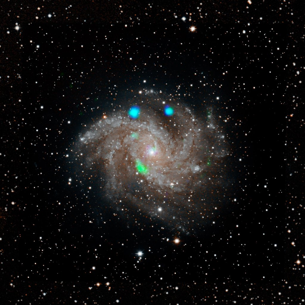 This visible-light image of the Fireworks galaxy (NGC 6946) comes from the Digital Sky Survey, and is overlaid with data from NASA's NuSTAR observatory (in blue and green).