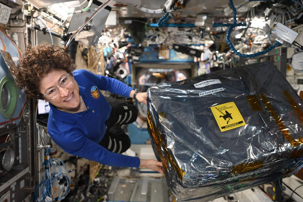 This image shows astronaut Christina Koch unloading new hardware for the Cold Atom Lab aboard the International Space Station the week of Dec. 9, 2020.