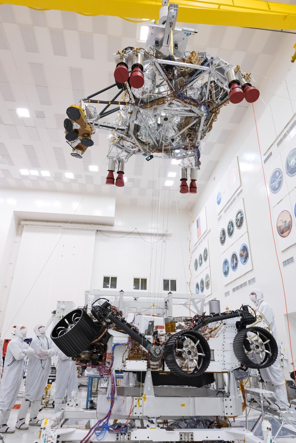 In this picture from Sept. 28, 2019, engineers and technicians working on the Mars 2020 spacecraft at NASA's Jet Propulsion Laboratory in Pasadena, California, look on as a crane lifts the rocket-powered descent stage away from the rover after a test.