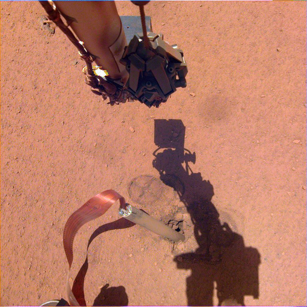The shadow of NASA InSight's robotic arm moves over its heat probe on Nov. 3, 2019, the 333rd Martian day, or sol, of the mission.