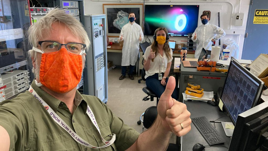 Thumbs-up for a successful test. Psyche engineers test an electric Hall thruster identical to those that will propel NASA's Psyche spacecraft on its journey to the asteroid Psyche.