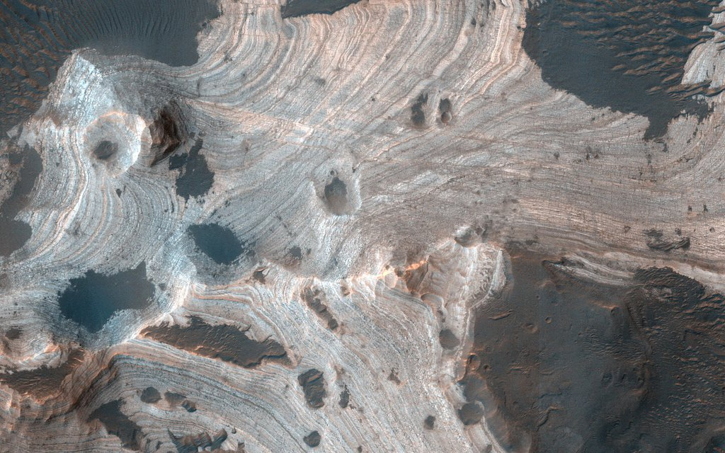 This image acquired on April 13, 2020 by NASA's Mars Reconnaissance Orbiter, reveals exquisite layering emerging from the sand in southern Holden Crater.