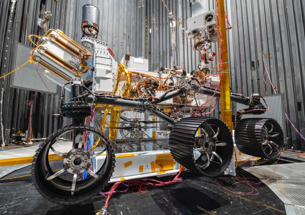 The Ingenuity Mars Helicopter can be seen between the left and center wheels of the Mars 2020 Perseverance rover. The image was taken in the vacuum chamber at JPL on Oct. 1, 2019.