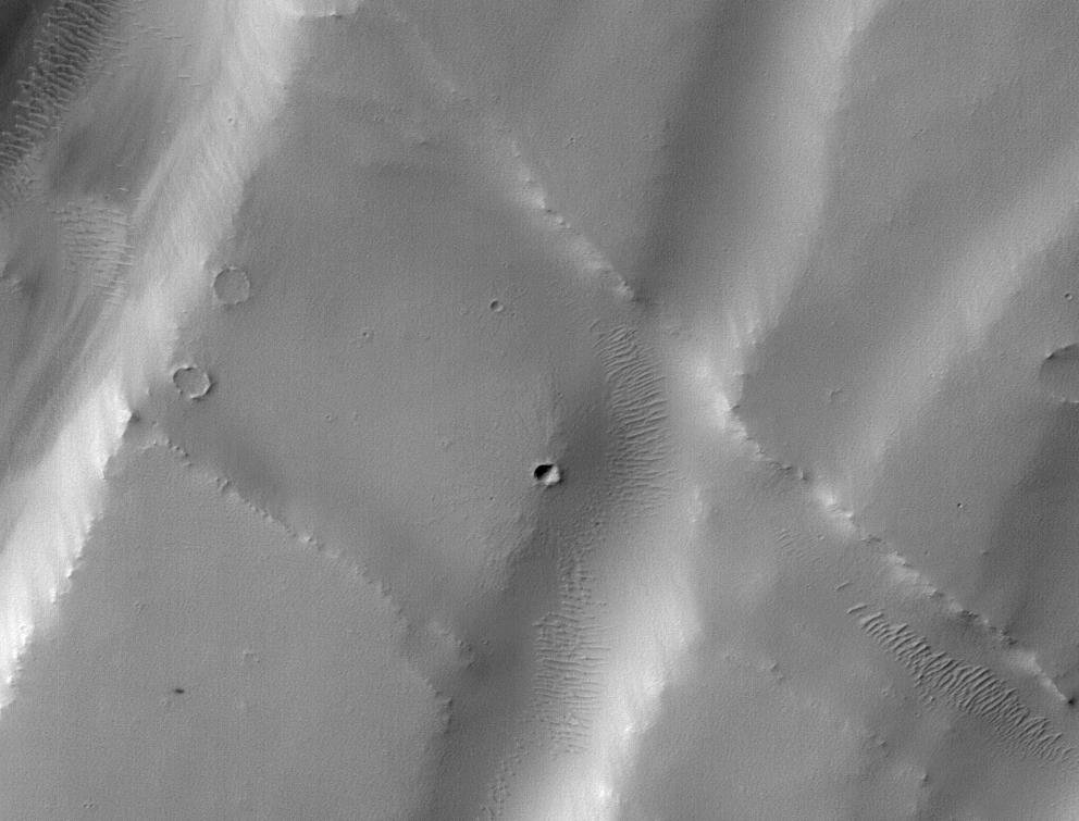 The black speck circled in the lower left corner of this image is a cluster of recently formed craters spotted on Mars using a new machine-learning algorithm. This image was taken by the Context Camera aboard NASA's Mars Reconnaissance Orbiter.