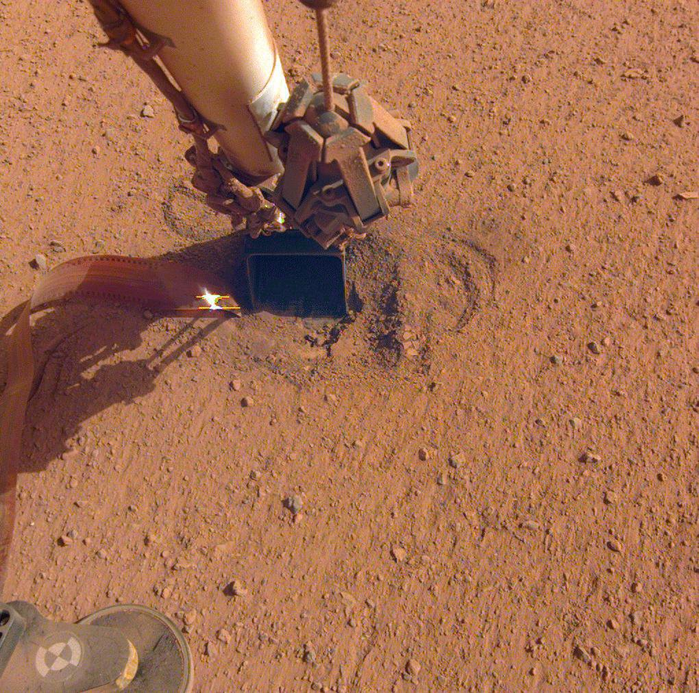 NASA's InSight retracted its robotic arm on Oct. 3, 2020, revealing where the spike-like mole is trying to burrow into Mars. In the coming months, the arm will scrape and tamp down soil on top of the mole to help it dig.