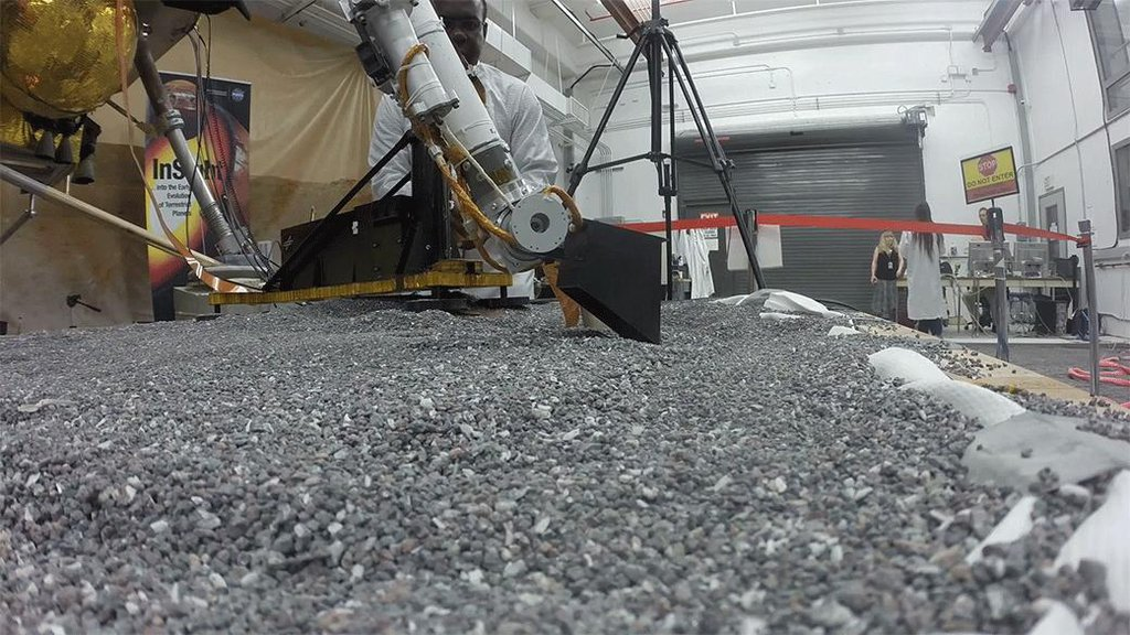 This footage from Aug. 19, 2019, shows a replica of InSight scraping soil with a scoop on the end of its robotic arm in a test lab at JPL. On Mars, InSight will scrape and tamp down soil on top of the mole to help it dig.