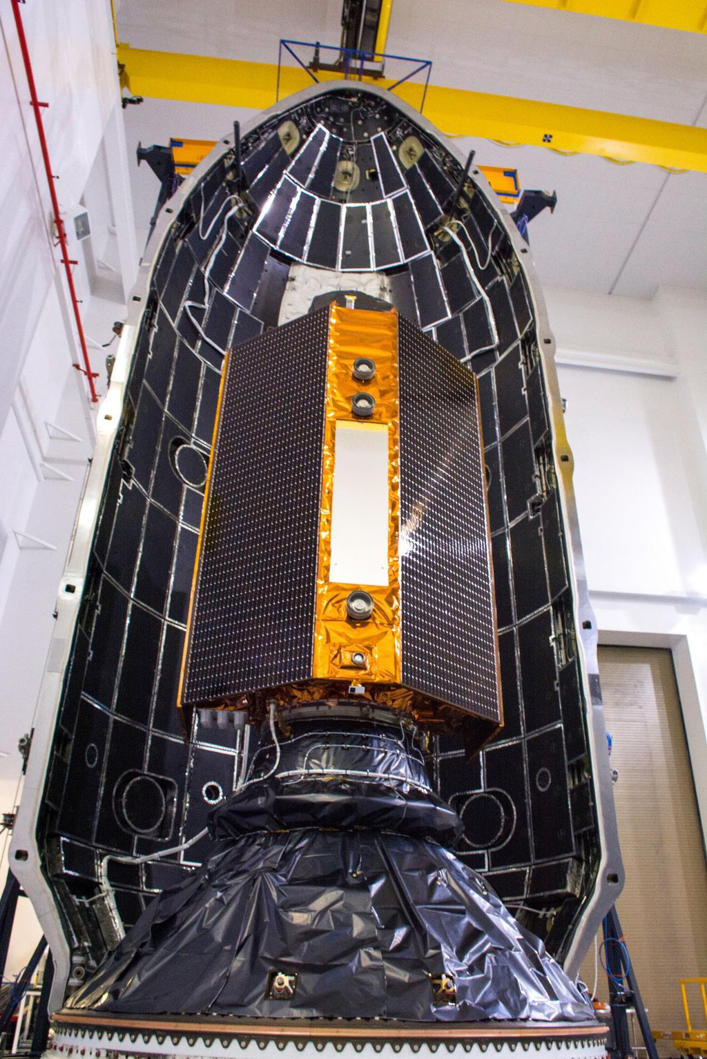 The Sentinel-6 Michael Freilich satellite is encapsulated in a protective nosecone, or payload fairing, at Vandenberg Air Force Base in California. The fairing will sit atop a SpaceX Falcon 9 rocket that will launch the satellite into Earth orbit.