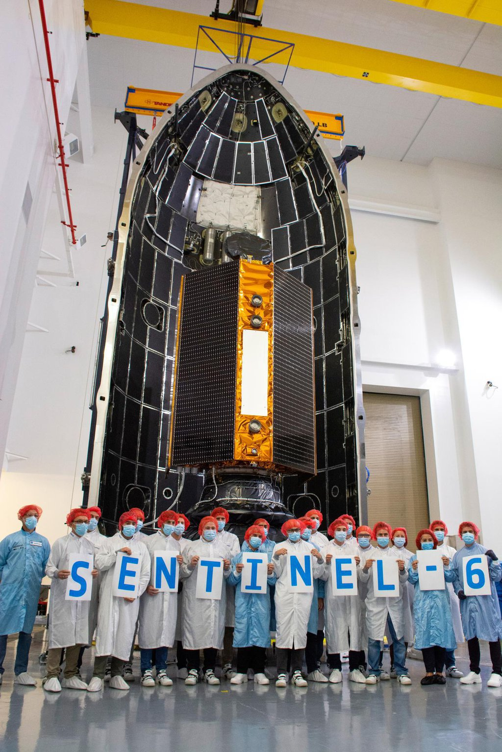 Technicians and engineers working on the Sentinel-6 Michael Freilich satellite pose in front of the spacecraft in its protective nosecone, or payload fairing, at Vandenberg Air Force Base in California.