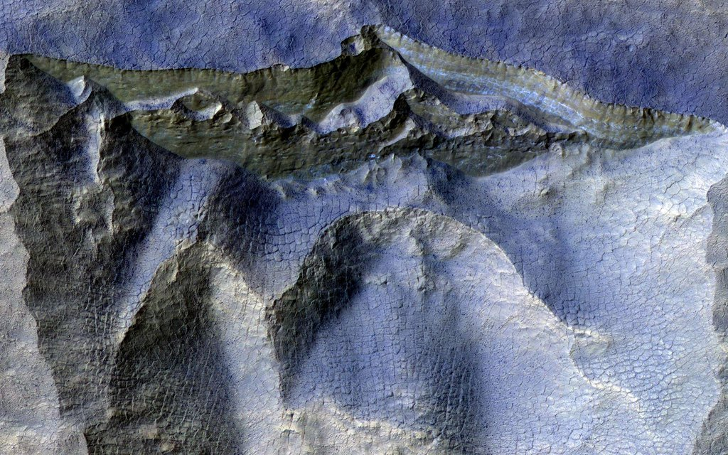 This image acquired on August 15, 2020 by NASA's Mars Reconnaissance Orbiter, shows a brownish, dusty cliff wall, where the faint light-blue-colored ice shows through.
