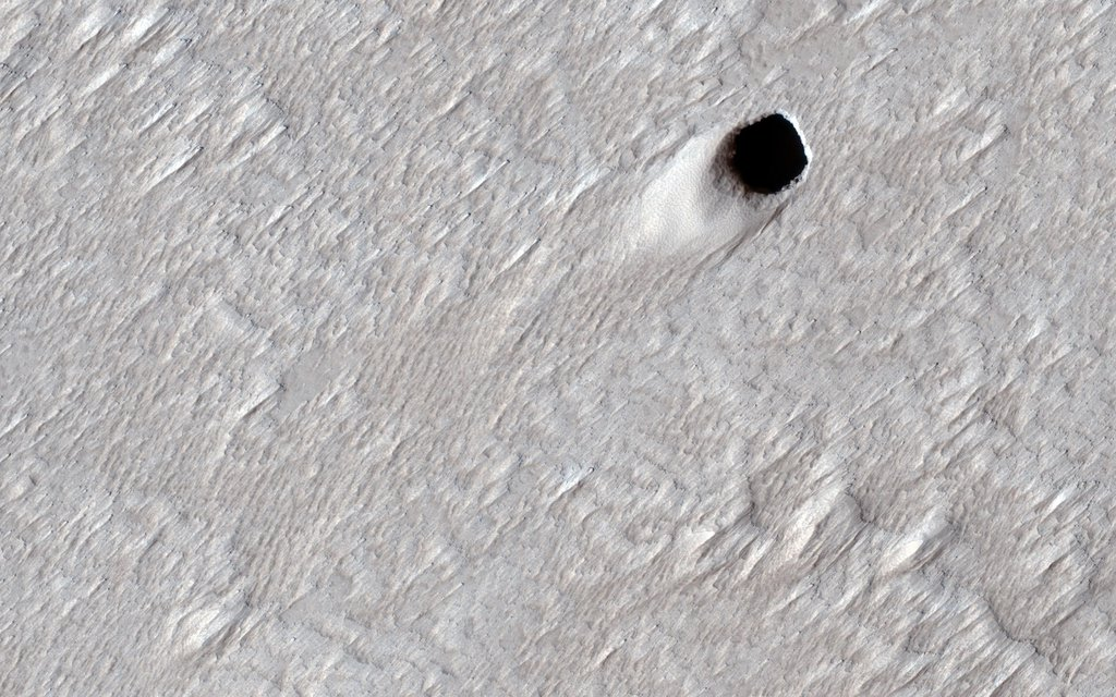 This image acquired on August 16, 2020 by NASA's Mars Reconnaissance Orbiter, shows the ceiling of a lava tube has collapsed in one spot and made this pit crater.