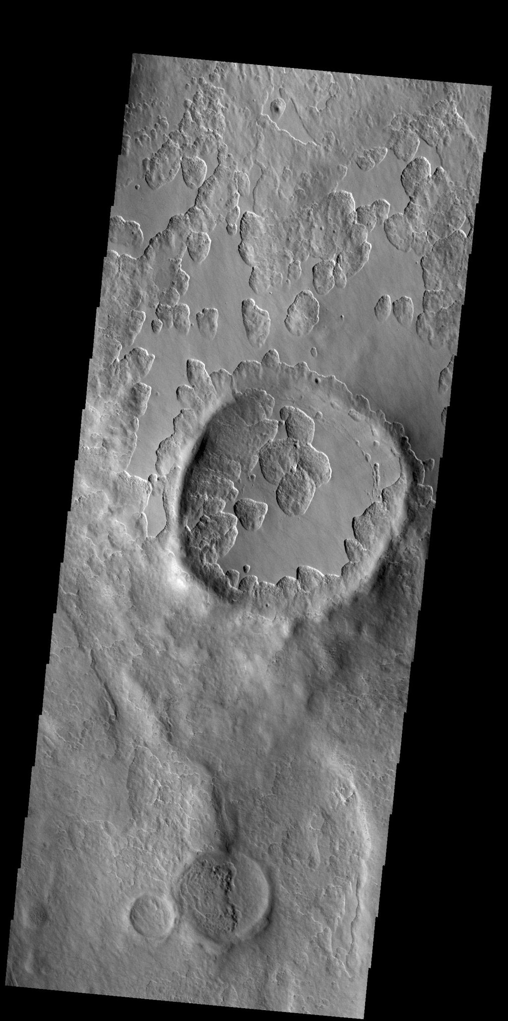 This image from NASA's Mars Odyssey shows an unusual layer of smooth material covers the flanks of the volcano Peneus Patera just south of the Hellas Basin.