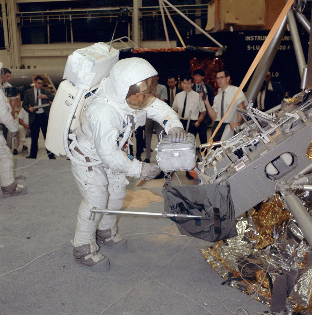 Apollo 11 commander Neil Armstrong works with an Apollo Lunar Sample Return Container during a lunar surface simulation training exercise in Building 9, Manned Spacecraft Center in Houston, Texas.